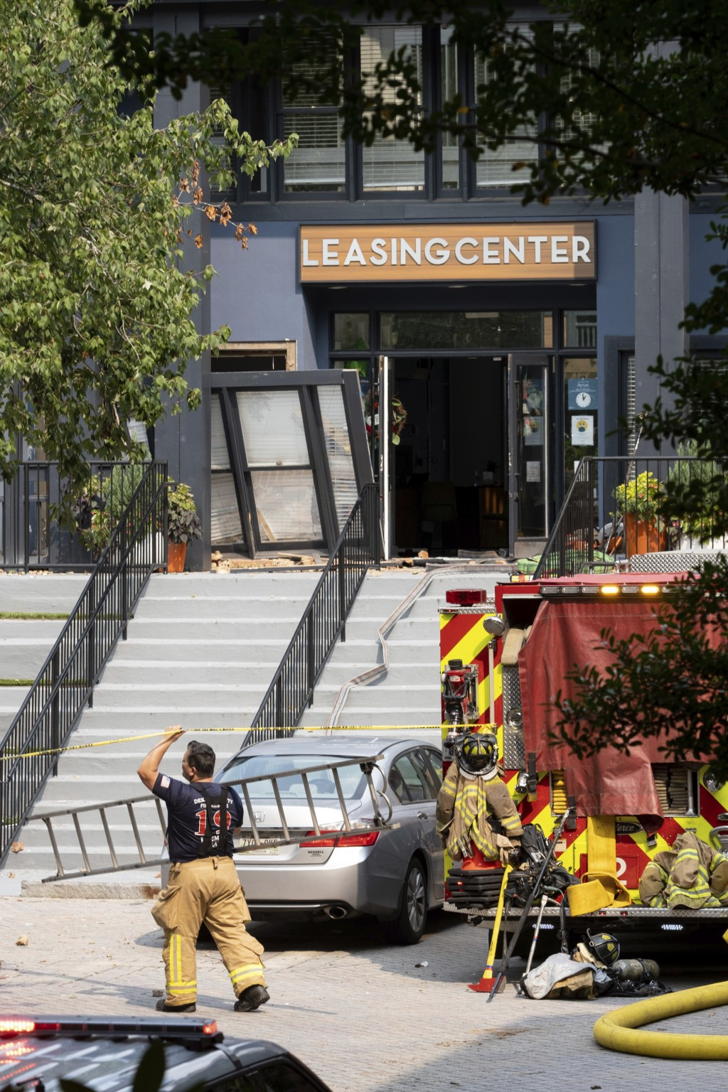 A firefighter carries a ladder past the damaged leasing center following an apartment building explosion, Sunday, Sept. 12, 2021, in Dunwoody, Ga., ju...