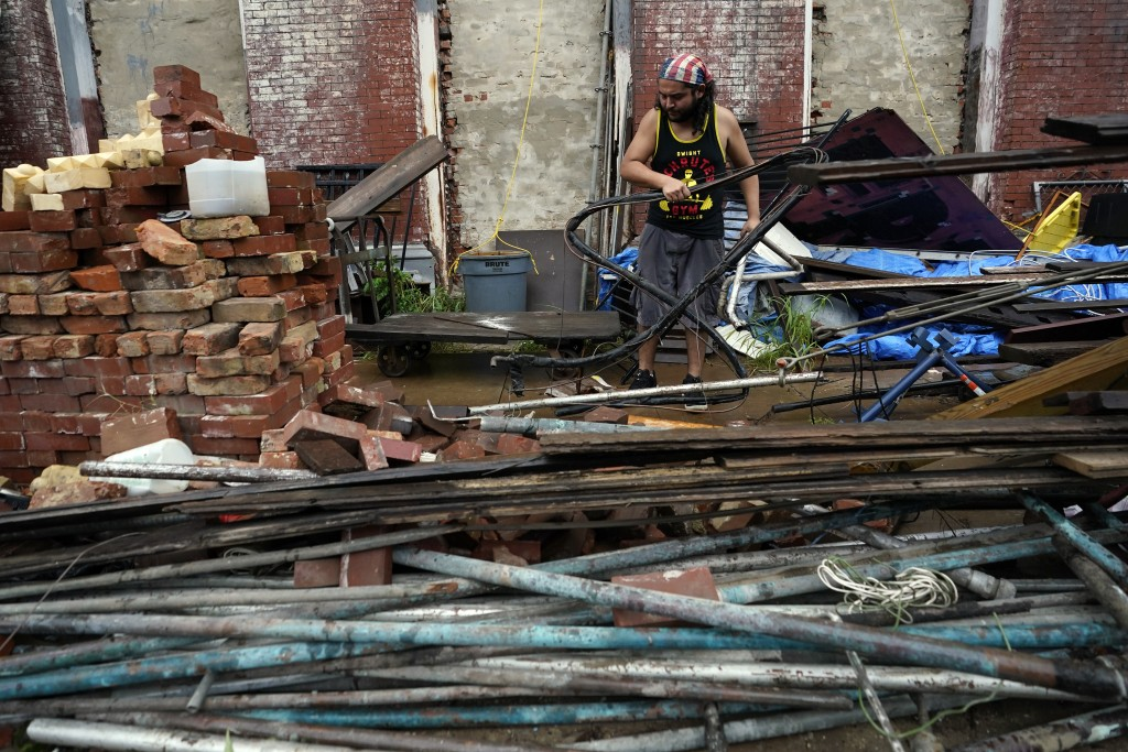 Adrian Bentancourt cleans up debris from a fence that was blow down by Hurricane Nicholas Tuesday, Sept. 14, 2021, in Galveston, Texas. (AP Photo/Davi...