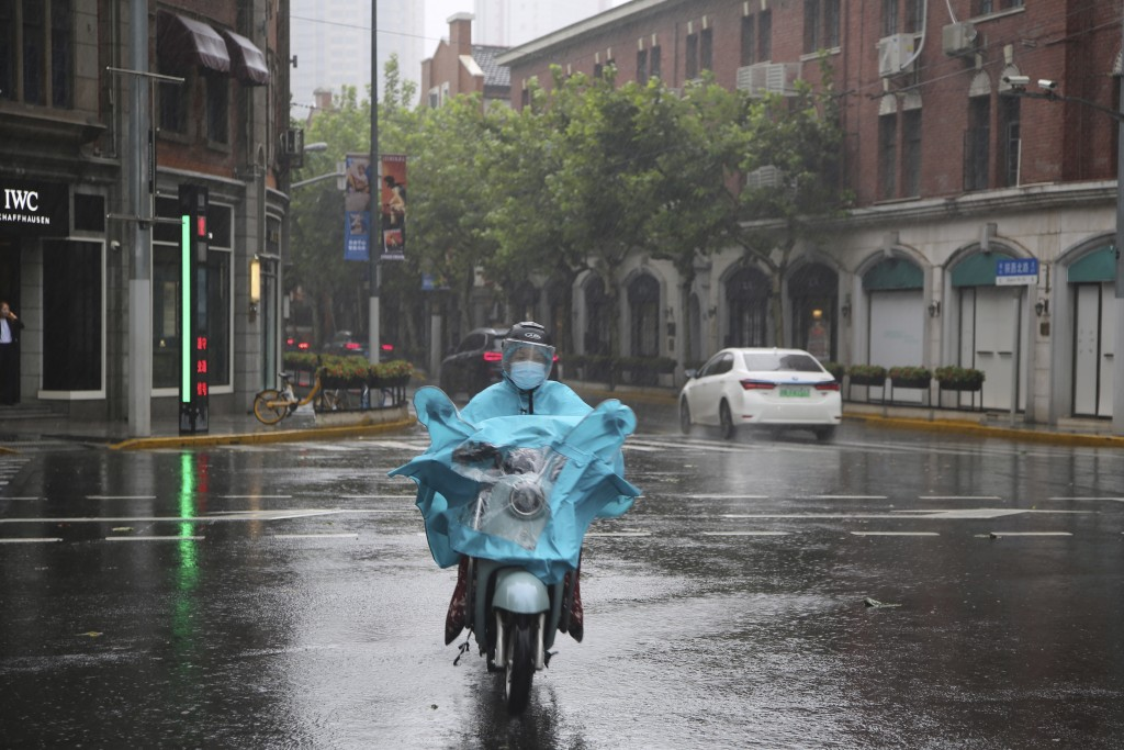 A resident wearing a mask and rain gear rides on the street as it rains in Shanghai, China, Monday, Sept. 13, 2021. Flights and train service were bei...