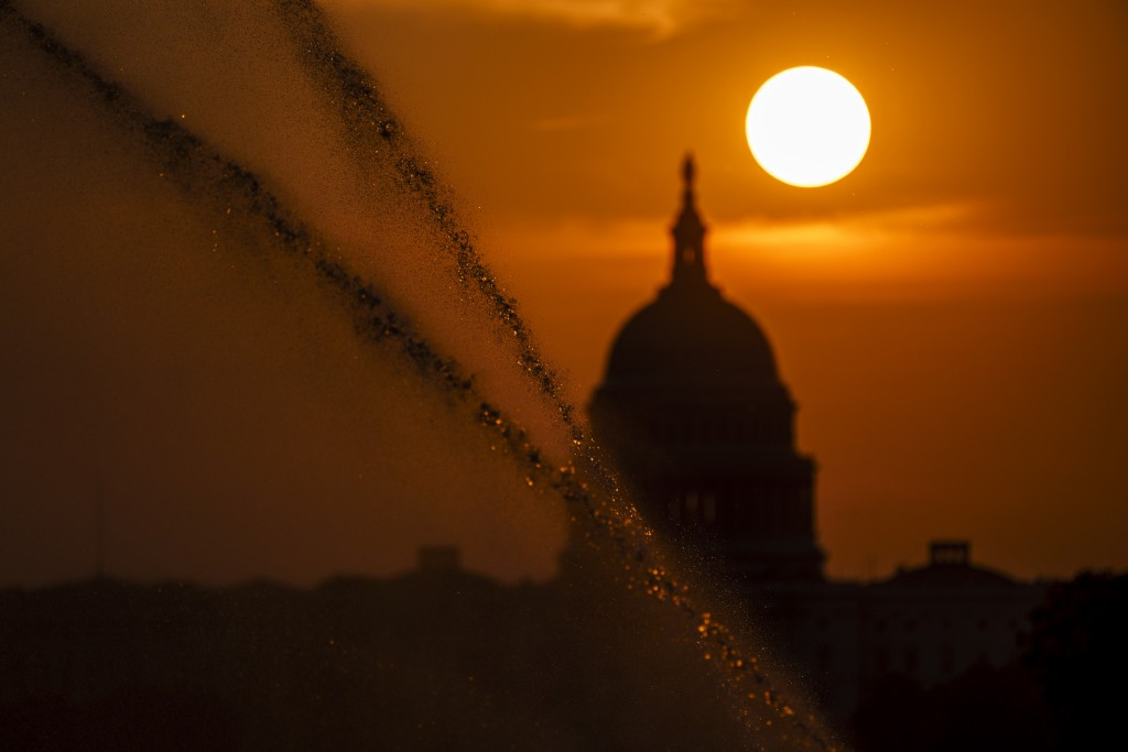 Sprinklers shoot jets of water along the National Mall as the sun rises behind the Capitol in Washington, Wednesday, Sept. 15, 2021. (AP Photo/J. Scot...