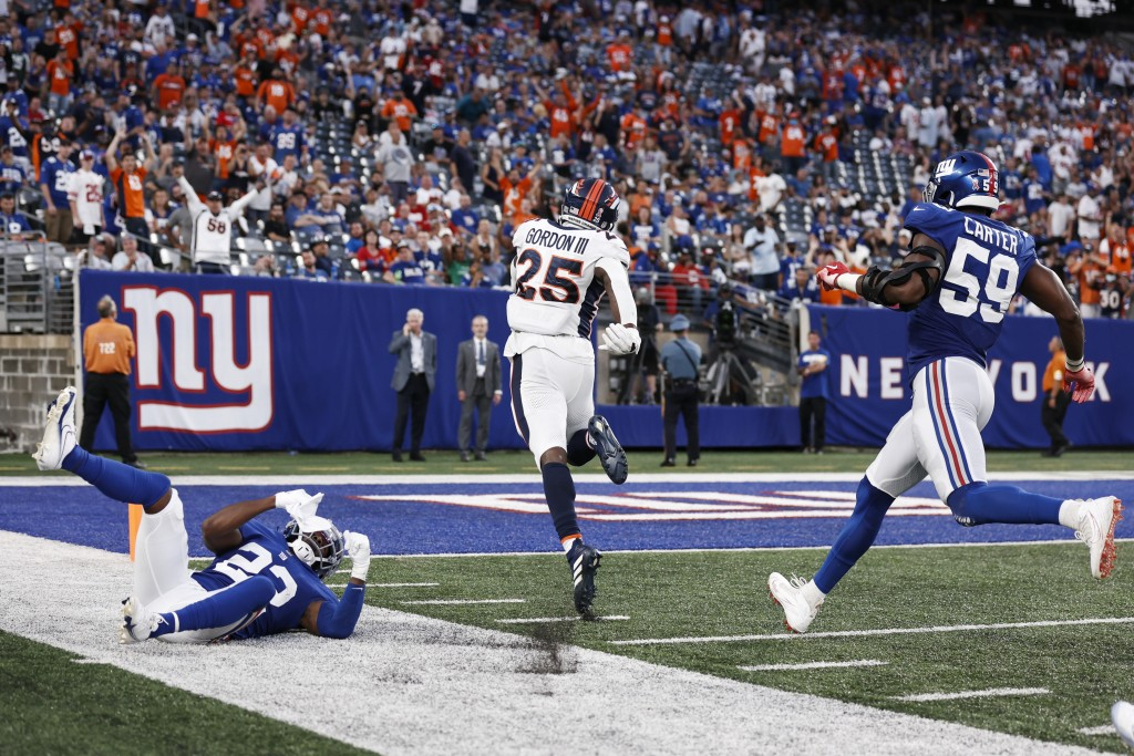 Denver Broncos running back Melvin Gordon (25) runs past New York Giants' Adoree' Jackson (22) and Lorenzo Carter (59) for a touchdown during the seco...