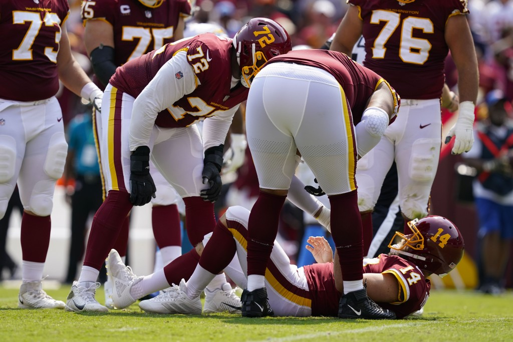 Members of the Washington Football Team check on condition of teammate quarterback Ryan Fitzpatrick (14) who lays on the field after being injured on ...