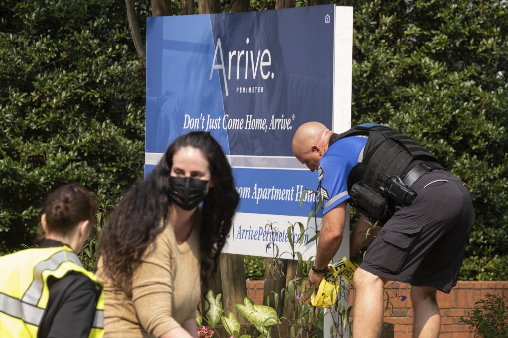 A police officer ties caution tape to the Arrive Perimeter apartment complex sign following an explosion at the complex, Sunday, Sept. 12, 2021, in Du...