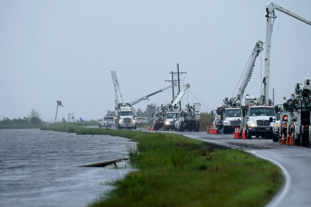 Utility crews replace power poles destroyed by Hurricane Ida as Tropical Storm Nicholas approaches in Pointe-aux-Chenes, La., Tuesday, Sept. 14, 2021....
