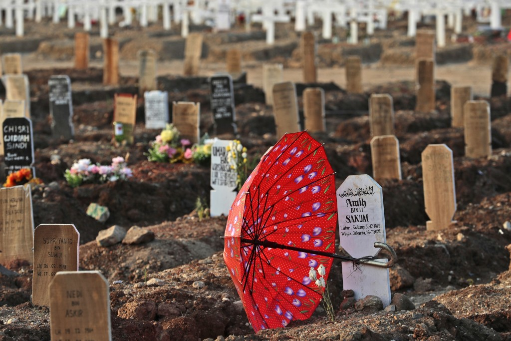 An umbrella lays at the grave of a woman who died of COVID-19 complications at Rorotan Cemetery in Jakarta, Indonesia, Wednesday, Aug. 25, 2021. In a ...