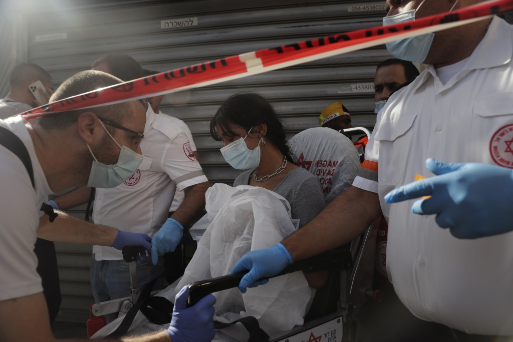 Israeli medics evacuate a woman from the site of a stabbing attack in Jerusalem's Central Bus Station Monday, Sept. 13, 2021. Israeli paramedics treat...