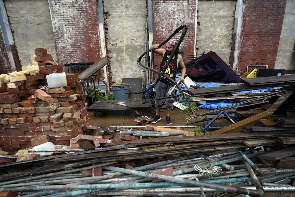 Adrian Bentancourt cleans up debris from a fence that was blown down by Hurricane Nicholas Tuesday, Sept. 14, 2021, in Galveston, Texas. (AP Photo/Dav...