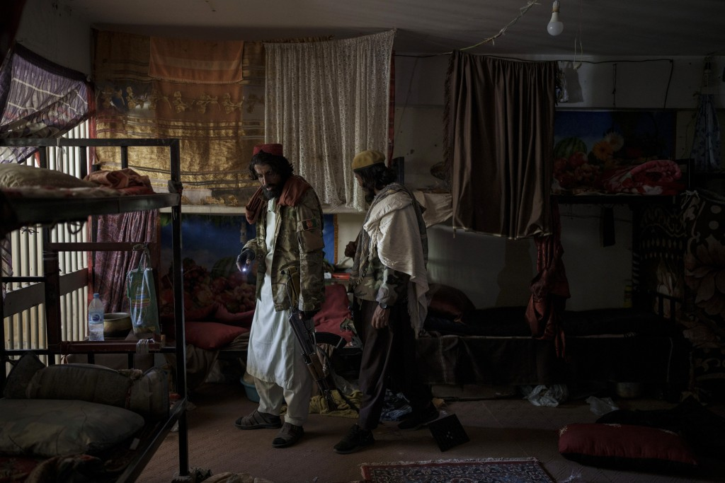 Taliban fighters walk inside an empty cell at the Pul-e-Charkhi prison in Kabul, Afghanistan, Monday, Sept. 13, 2021. Pul-e-Charkhi was previously the...