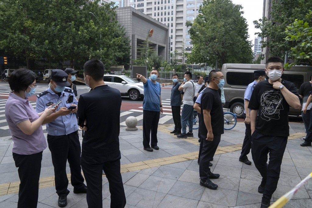 Plainclothes and uniformed police officers stand guard outside a courthouse in Beijing, Tuesday, Sept. 14, 2021. A young Chinese woman headed to court...