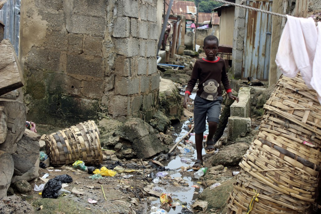 A boy walks past sewage around houses in Abuja, Nigeria, Friday, Sept. 3, 2021. Nigeria is seeing one of its worst cholera outbreaks in years, with mo...