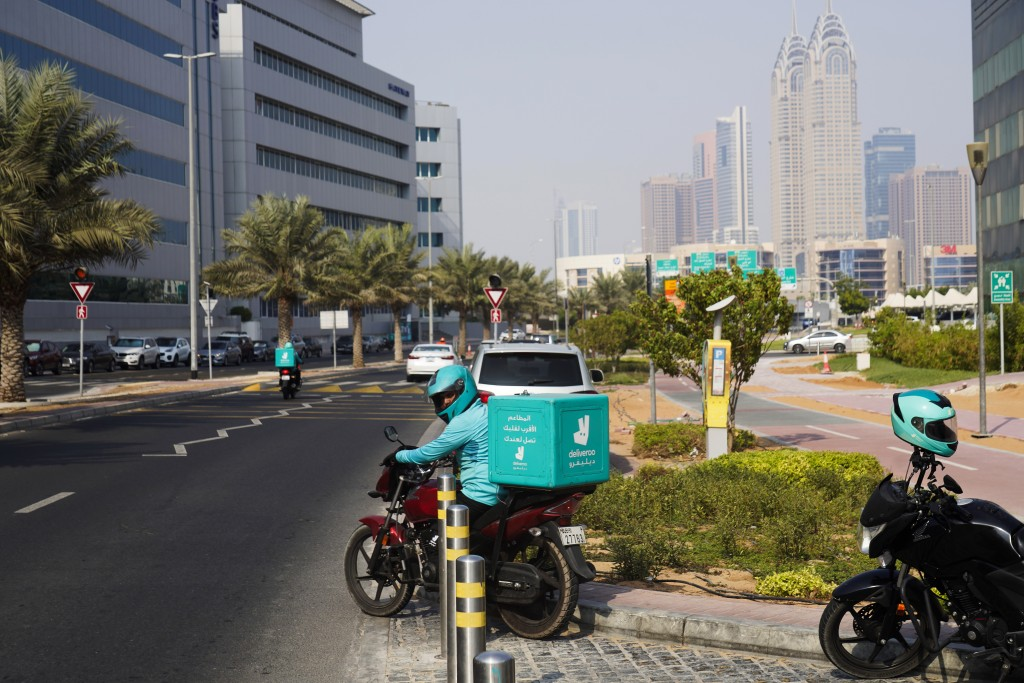 A delivery driver for the app Deliveroo prepares to make a delivery, in Dubai, United Arab Emirates, Thursday, Sept. 9, 2021. Advocates and workers sa...