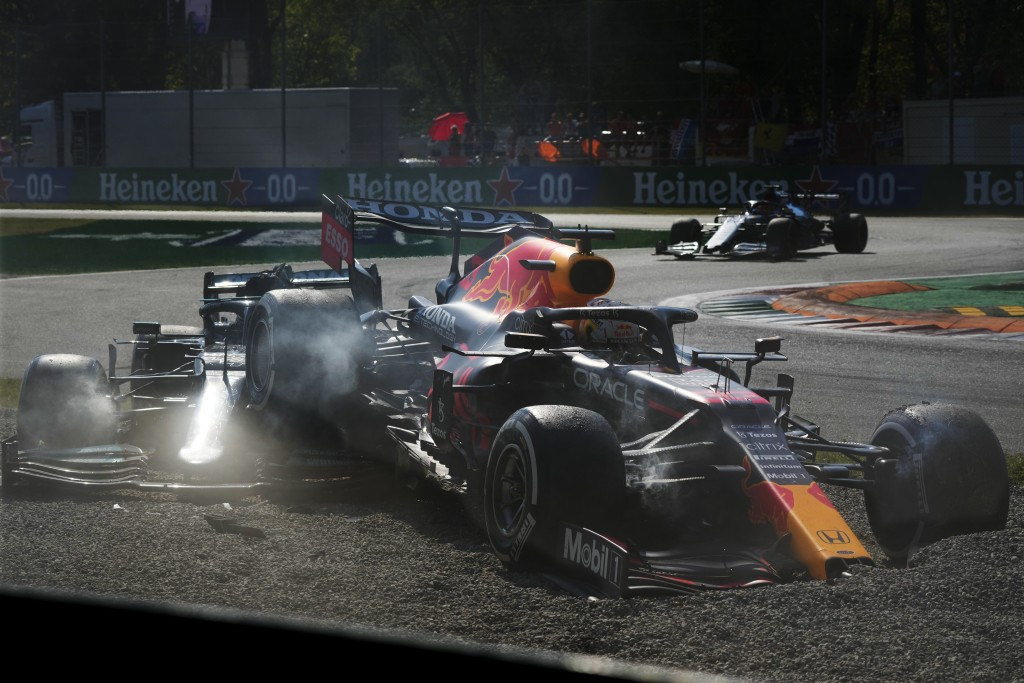 Red Bull driver Max Verstappen of the Netherlands, right and Mercedes driver Lewis Hamilton of Britain crash during the Italian Formula One Grand Prix...