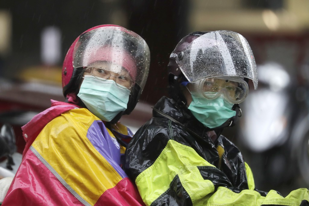 People ride a motorbike in the rain caused by Typhoon Chanthu in Taipei, Taiwan, Sunday, Sept. 12, 2021. Typhoon Chanthu drenched Taiwan with heavy ra...