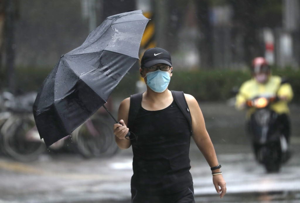 A man struggles with his umbrella against powerful gusts of wind generated by Typhoon Chanthu in Taipei, Taiwan, Sunday, Sept. 12, 2021. Typhoon Chant...