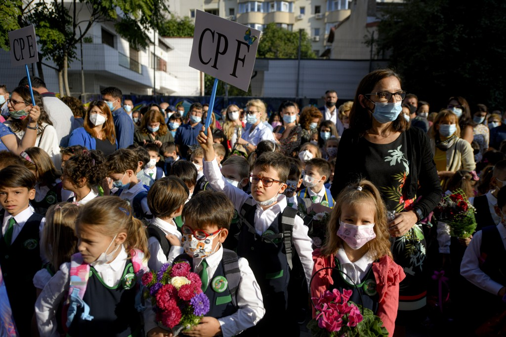 Children wearing face masks react during festivities marking the beginning of the school year at a school in Bucharest, Romania, Monday, Sept. 13, 202...