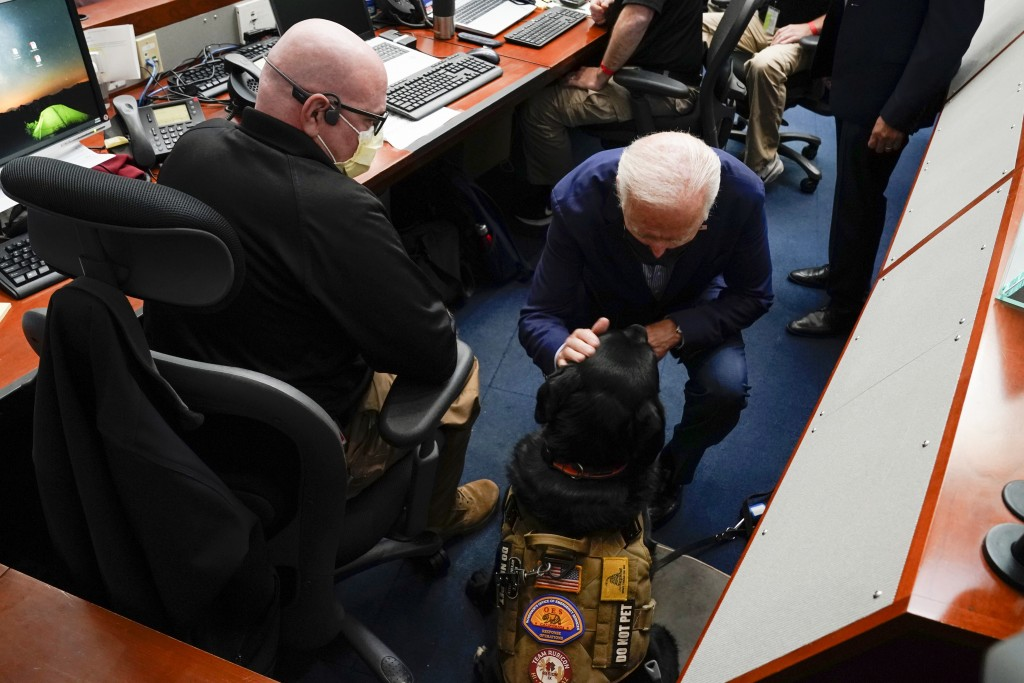President Joe Biden pets a service dog during a briefing on wildfires at the California Governor's Office of Emergency Services, Monday, Sept. 13, 202...
