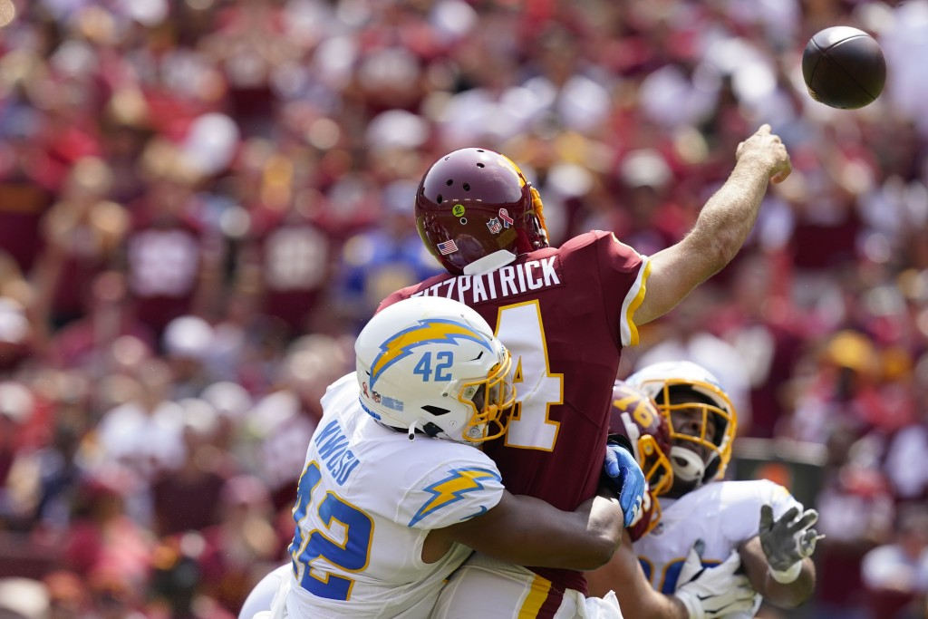 Washington Football Team quarterback Ryan Fitzpatrick (14) is hit from behind by Los Angeles Chargers linebacker Uchenna Nwosu (42), while throwing th...