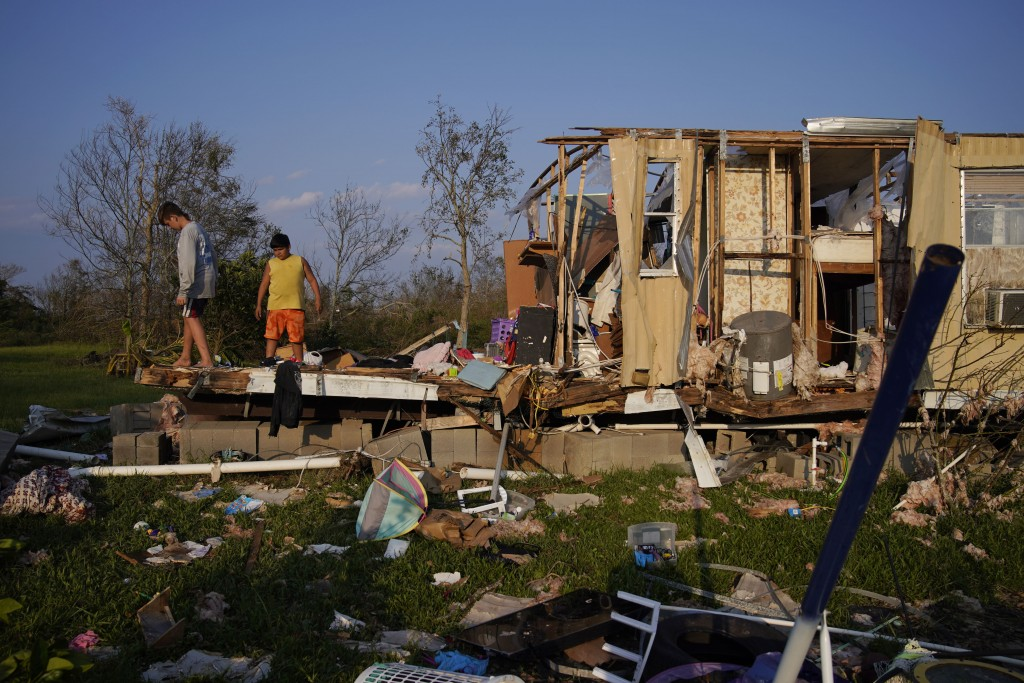 FILE - In this Sept. 4, 2021 file photo, Aiden Locobon, left, and Rogelio Paredes look through the remnants of their family's home destroyed by Hurric...