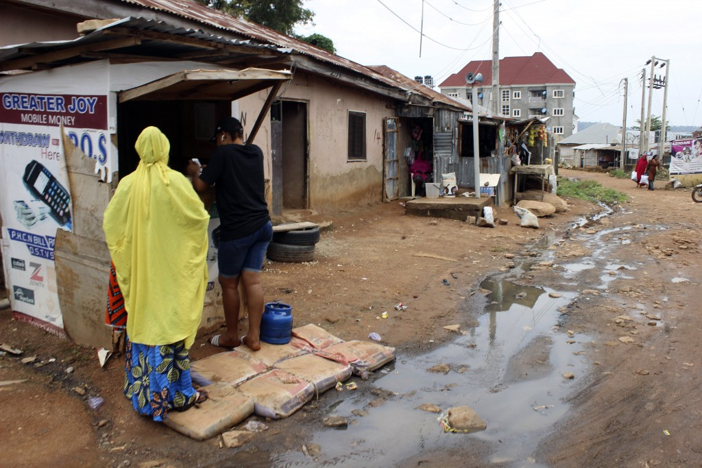 Two women buy mobile phone cards from a stall close to sewage water in Abuja, Nigeria, Friday, Sept. 3, 2021. Nigeria is seeing one of its worst chole...