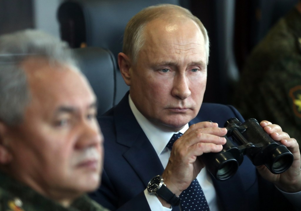 Russian President Vladimir Putin, right, holds a binoculars as Russian Defense Minister Sergei Shoigu sits near watching the joint strategic exercise ...