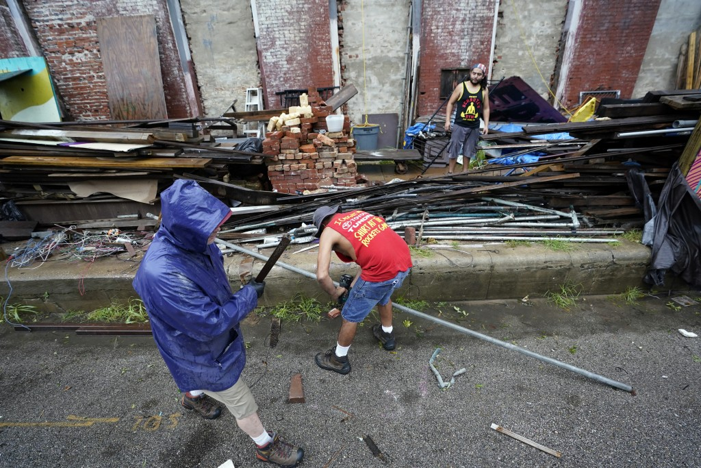 Larry Reed, left, Fred Williams, center, and Adrian Bentancourt clean up debris from a fence that was blown down by Hurricane Nicholas Tuesday, Sept. ...
