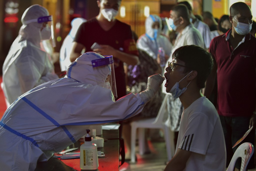 In this photo released by Xinhua News Agency, a health worker collects swab sample from a resident during a mass COVID-19 test in Putian in southeast ...