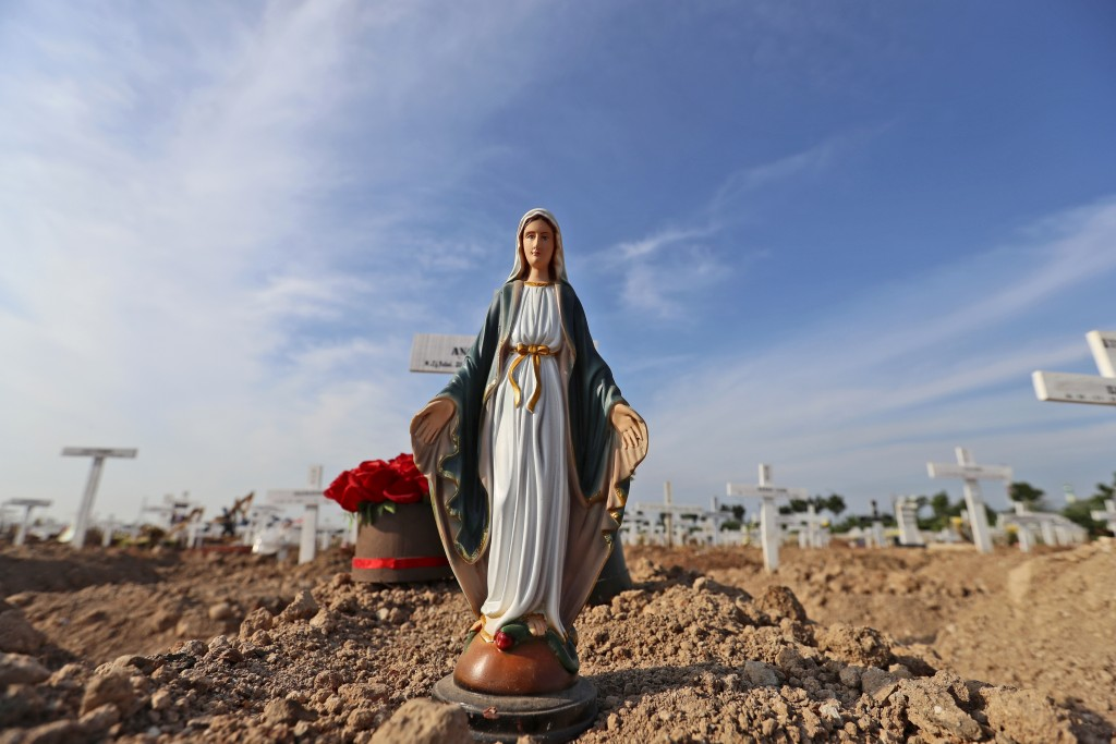 A statue of Virgin Mary is placed on the grave of a woman who died of COVID-19 at Rorotan Cemetery in Jakarta, Indonesia, Wednesday, Sept. 1, 2021. In...