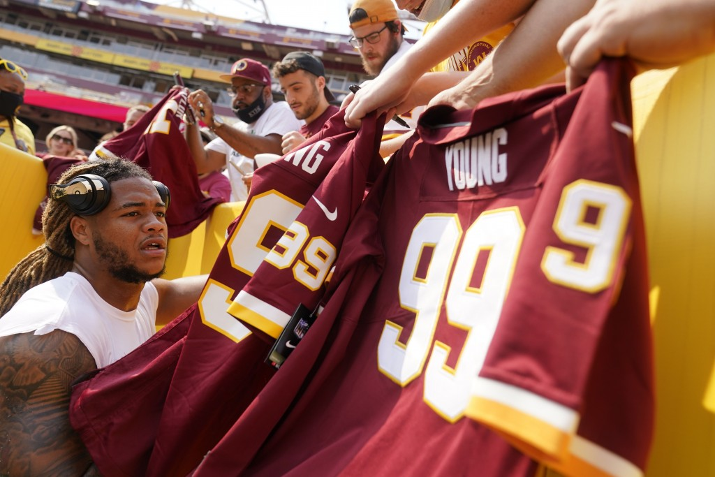 Washington Football Team defensive end Chase Young (99) signs autographs for fans before an NFL football game against the Los Angeles Chargers, Sunday...