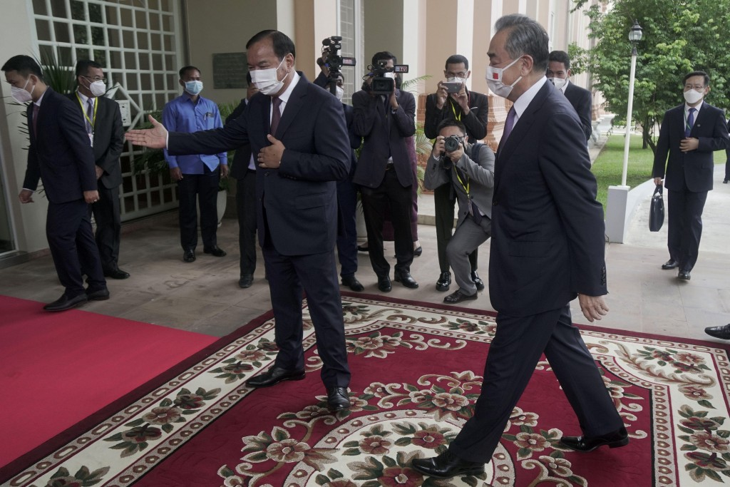 Chinese Foreign Minister Wang Yi, foreground right, is guided by his Cambodian counterpart Prak Sokhonn, center, in Phnom Penh, Cambodia, Sunday, Sept...
