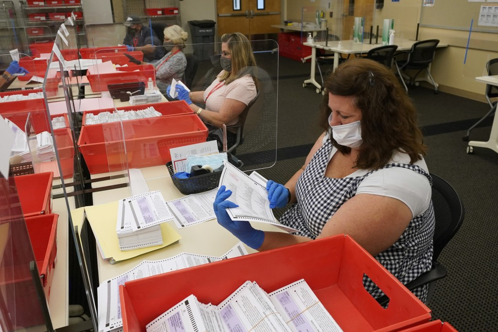 FILE — In this Aug. 30, 2021 file photo election workers inspect ballots for damage that have been received for the Sept. 14, recall election at the S...
