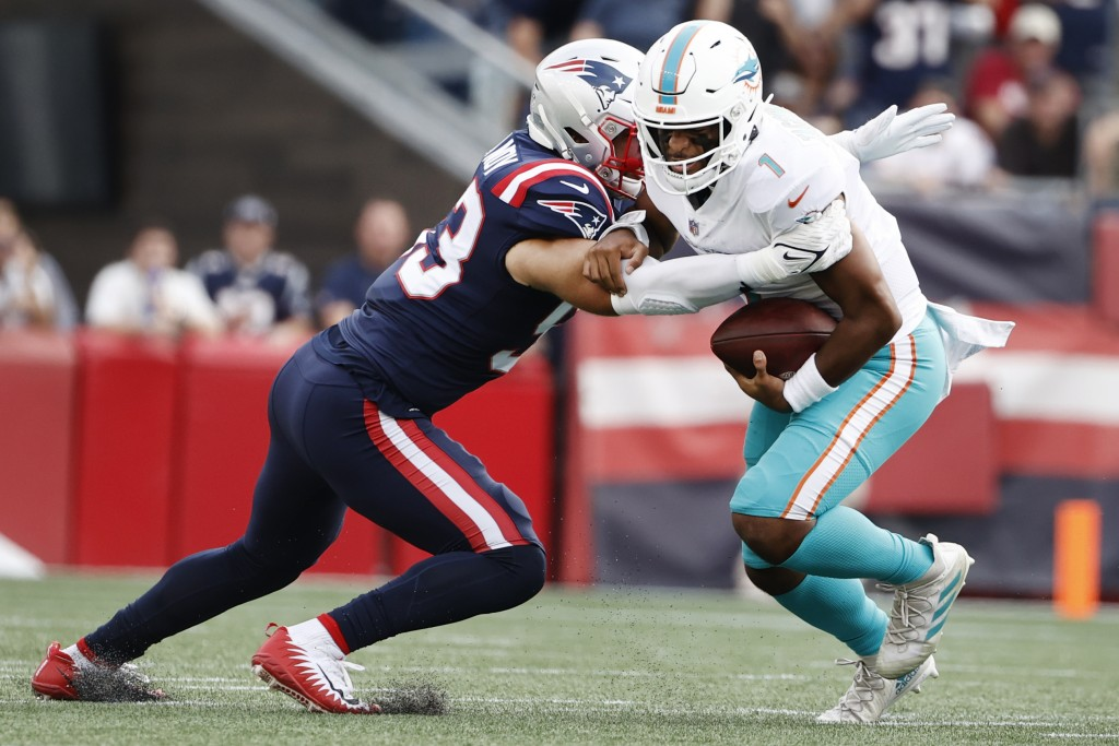New England Patriots middle linebacker Kyle Van Noy, left, takes down Miami Dolphins quarterback Tua Tagovailoa, right, during the first half of an NF...