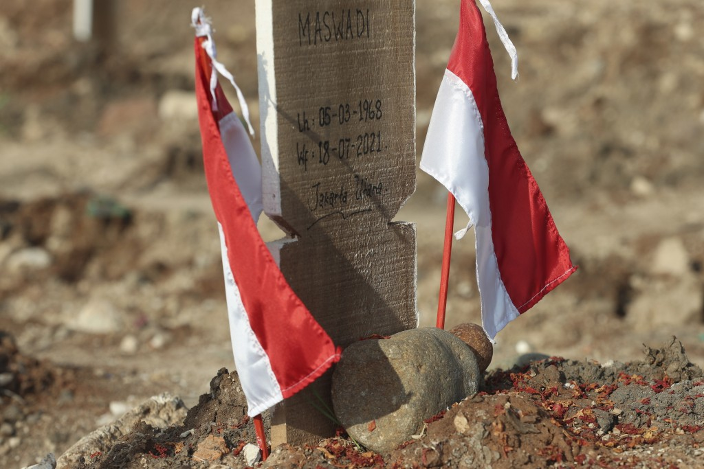 Indonesian national Red-White flags are put at the grave of a COVID-19 victim at Rorotan Cemetery in Jakarta, Indonesia, Wednesday, Sept. 1, 2021. In ...