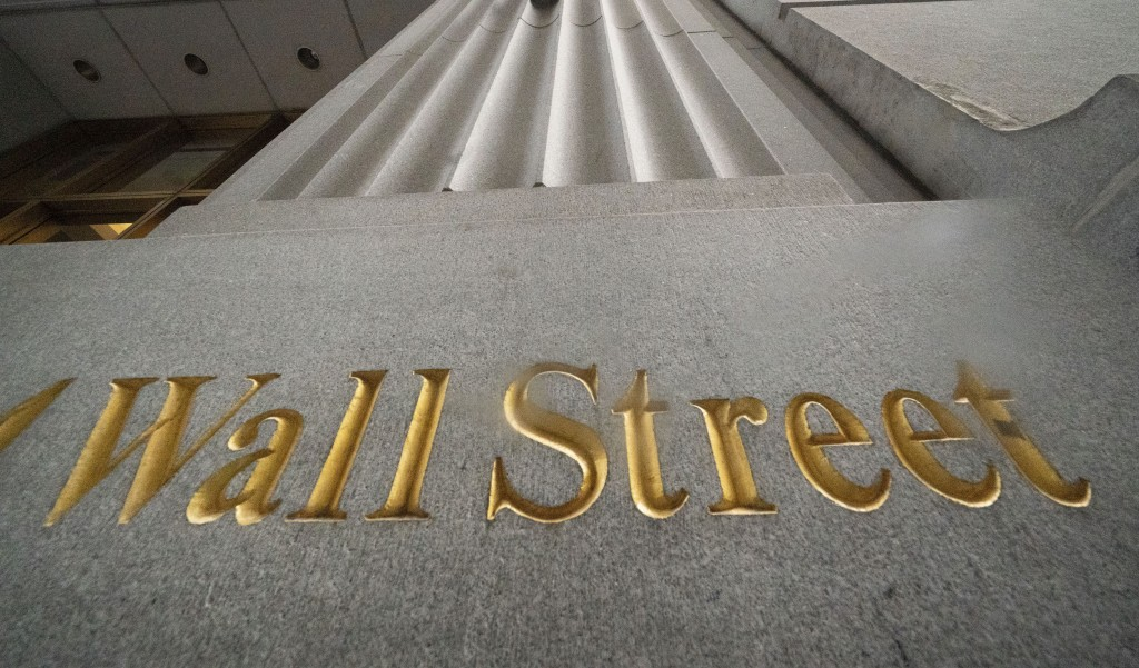 FILE - In this Nov. 5, 2020 file photo, a sign for Wall Street is carved in the side of a building, in New York.  Stocks are opening broadly higher on...