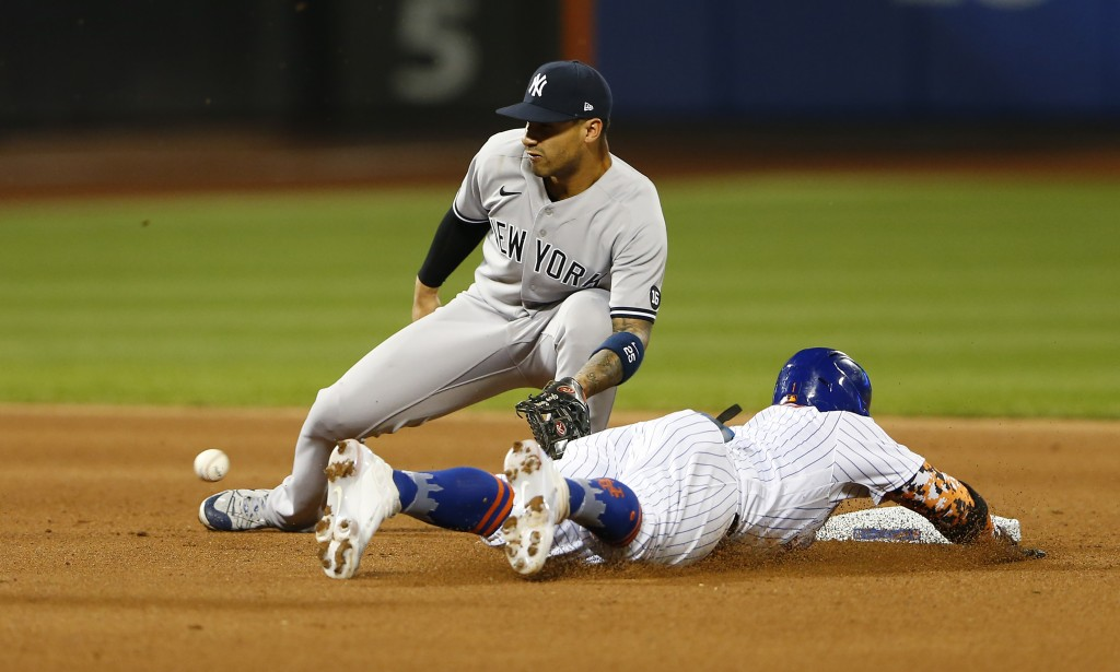 New York Mets' Jonathan Villar beats the throw to New York Yankees' Gleyber Torres for a stolen base during the fourth inning of a baseball game on Su...