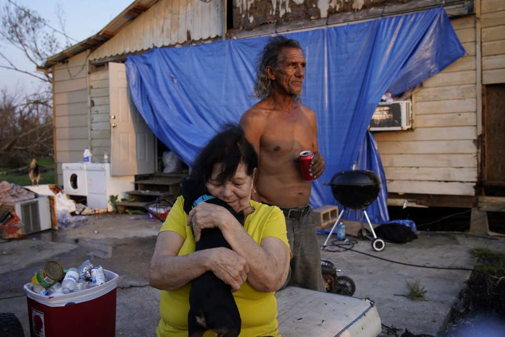 FILE - In this Sept. 4, 2021 file photo, Yvonne Lacobon hugs a dog beside Tommy Williams at Williams' home damaged by Hurricane Ida, in Dulac, La. Lou...
