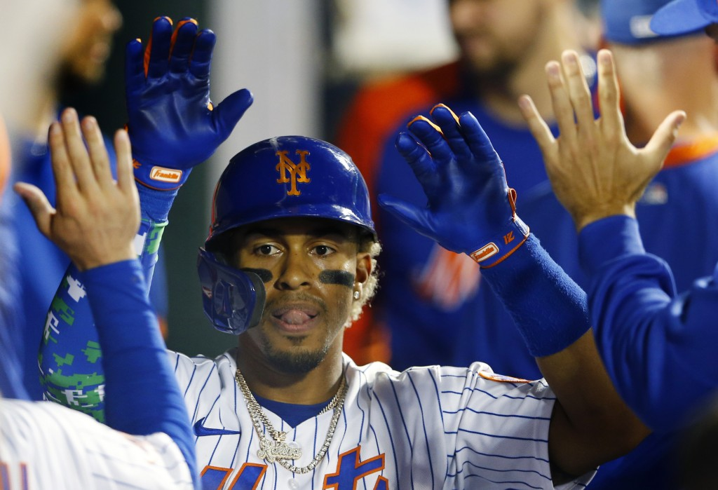 New York Mets' Francisco Lindor celebrates in the dugout after hitting a home run during the second inning of a baseball game against the New York Yan...