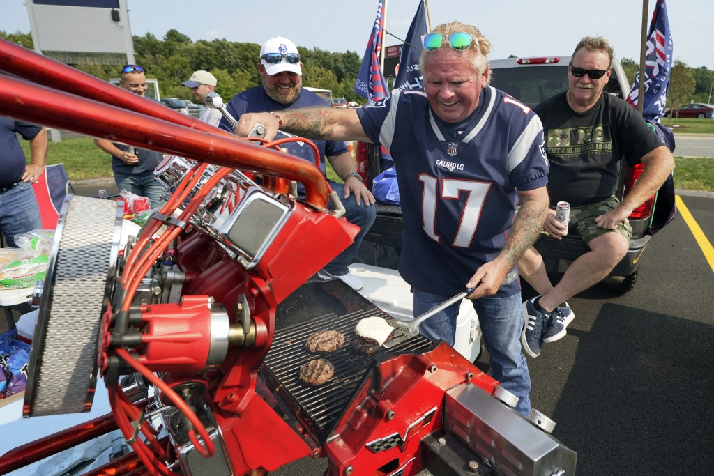 New England Patriots fan Billy Burrows, of Billerica, Mass., grills while tailgating prior to an NFL football game, Sunday, Sept. 12, 2021, in Foxboro...