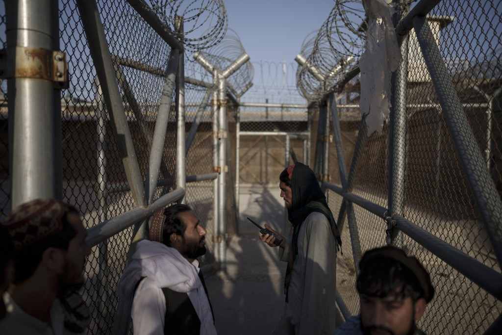 Taliban fighters enter an area where they are holding inmates who have been recently arrested at the Pul-e-Charkhi prison in Kabul, Afghanistan, Monda...
