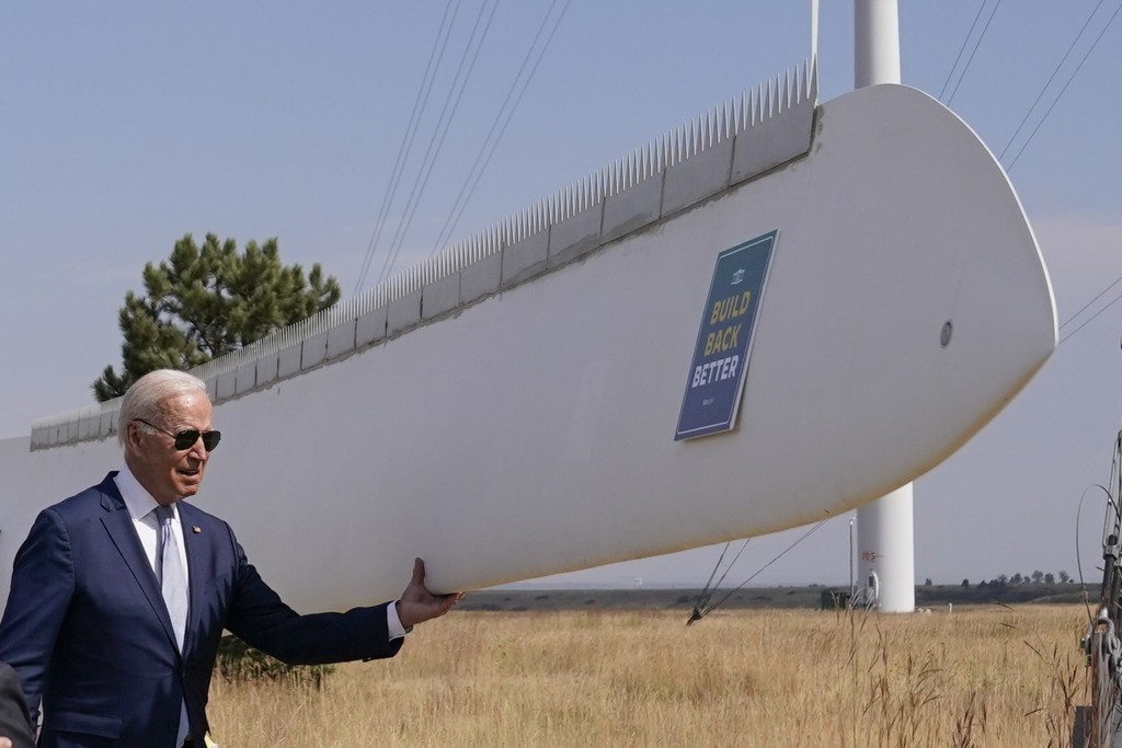President Joe Biden holds onto a wind turbine blade during a tour at the Flatirons campus of the National Renewable Energy Laboratory, Tuesday, Sept. ...