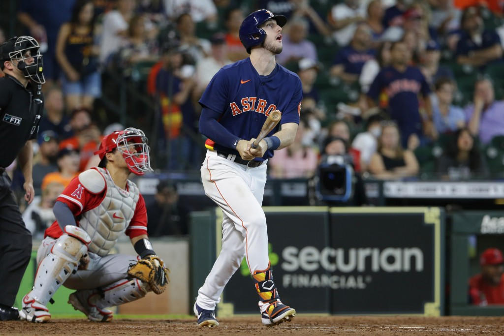 Houston Astros' Kyle Tucker, right, watches his two-run home run in front of Los Angeles Angels catcher Kurt Suzuki, second from left, during the sixt...