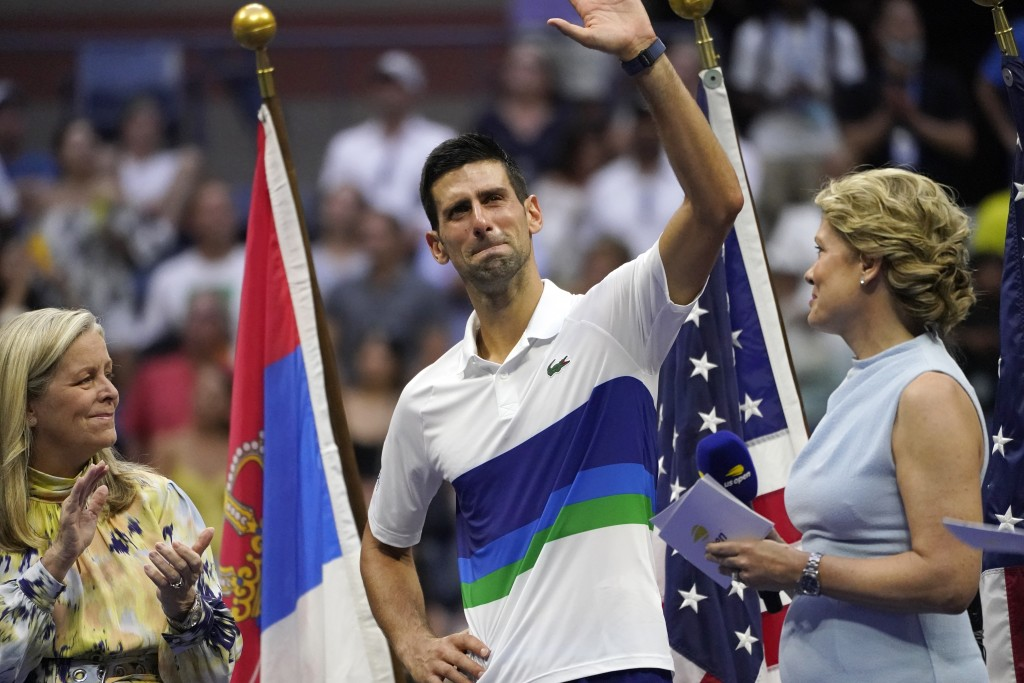 Novak Djokovic, of Serbia, center, waves to the crowd after losing to Daniil Medvedev, of Russia, in the men's singles final of the US Open tennis cha...