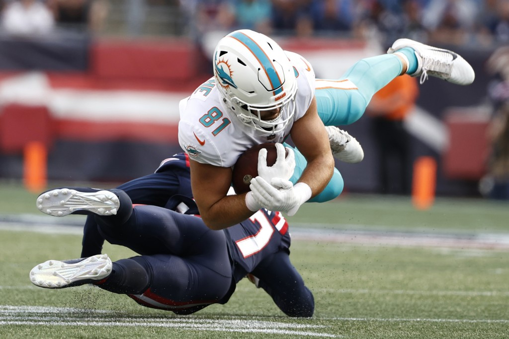 Miami Dolphins tight end Durham Smythe (81) hangs onto the ball while taken down by New England Patriots defensive back J.C. Jackson during the first ...