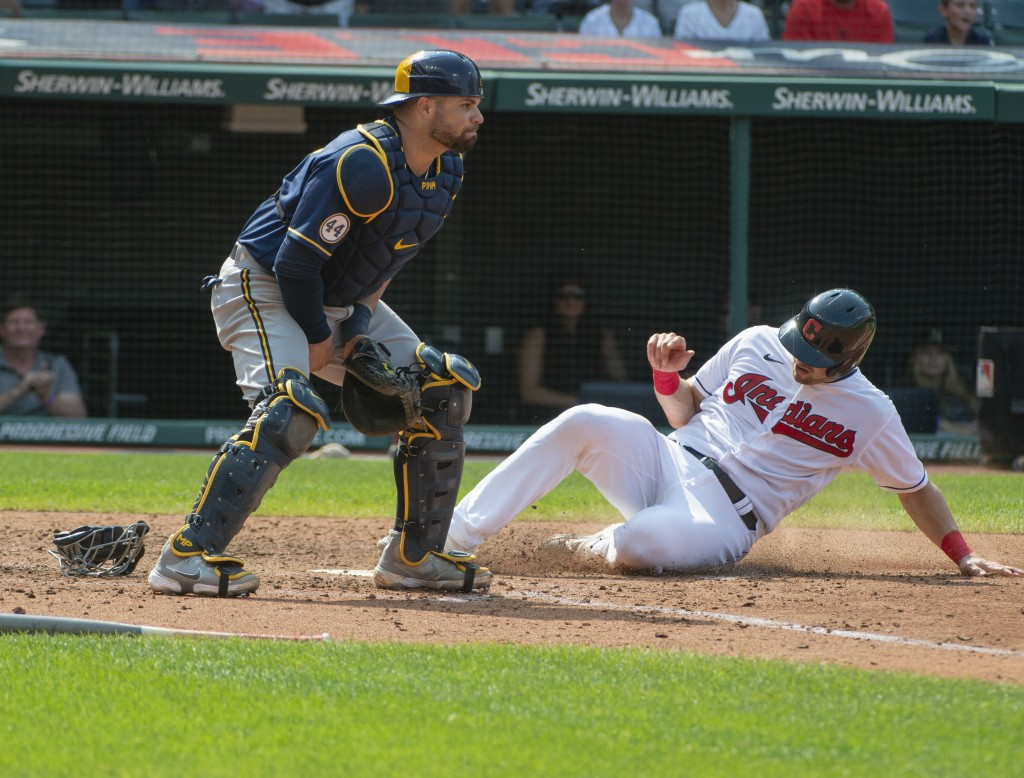 Cleveland Indians' Ryan Lavarnway scores on a single by Myles Straw as Milwaukee Brewers' Manny Pina waits for the throw during the sixth inning of a ...