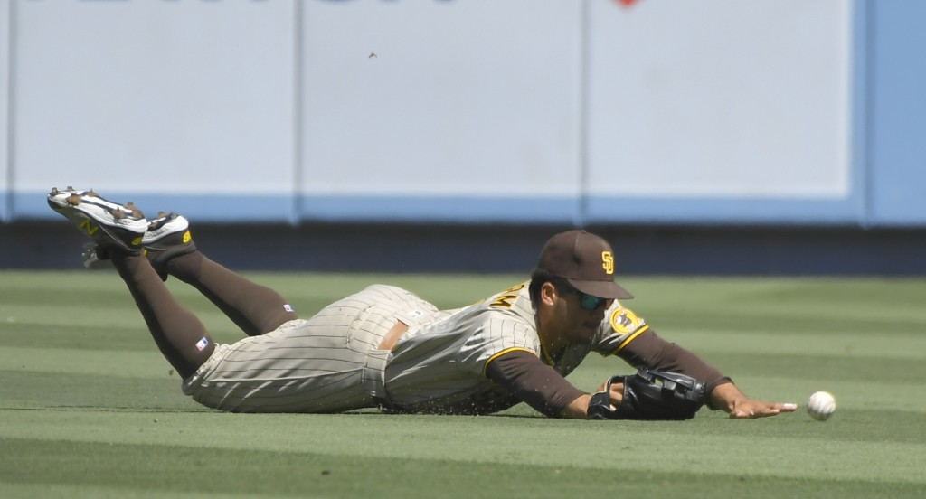 San Diego Padres center fielder Trent Grisham dives but cannot catch a fly ball hit by Los Angeles Dodgers' Trea Turner in the first inning during in ...