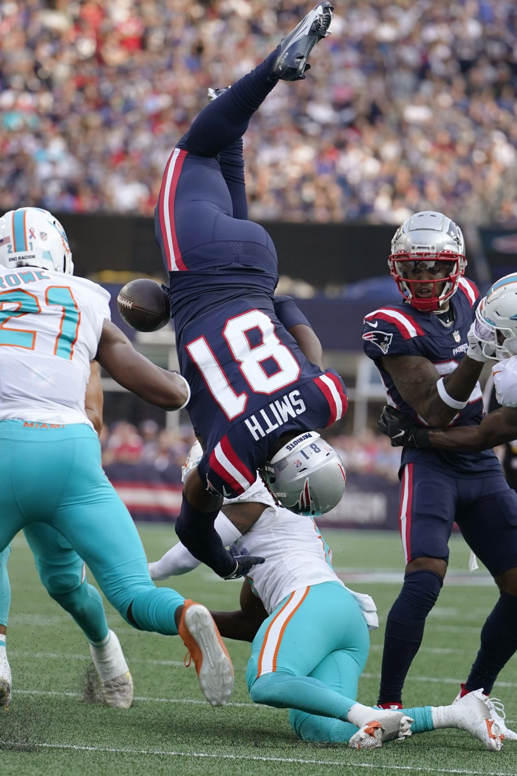 New England Patriots tight end Jonnu Smith (81) is upended by Miami Dolphins cornerback Justin Coleman during the first half of an NFL football game, ...