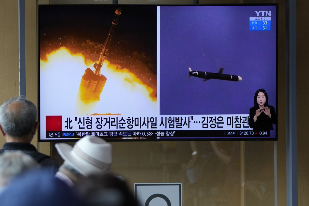 People watch a TV screen showing a news program reporting about North Korea's long-range cruise missiles tests with images in Seoul, South Korea, Mond...