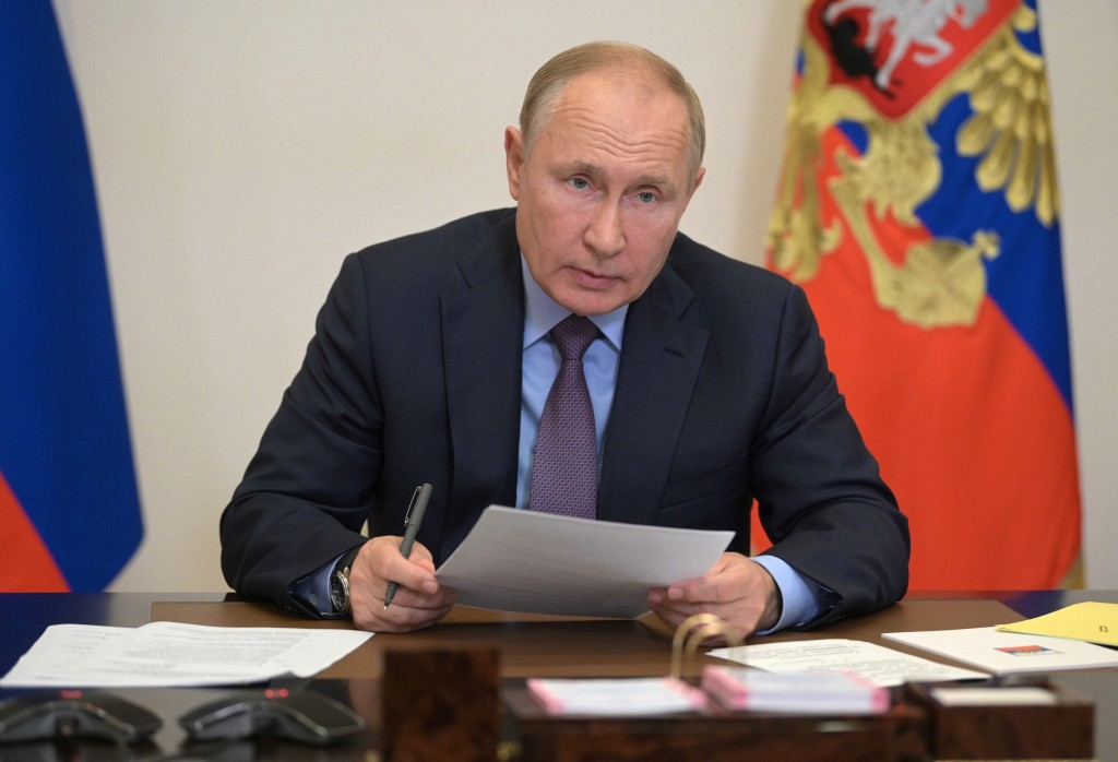 Russian President Vladimir Putin attends a meeting with members of Russian Government and heads of United Russia party via videoconference at the Novo...