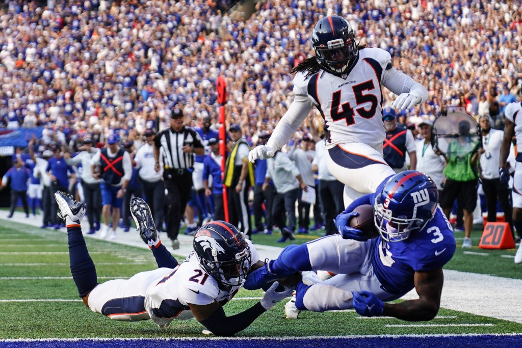 Denver Broncos' Ronald Darby (21) tackles New York Giants' Sterling Shepard (3) as Shepard scores a touchdown during the first half of an NFL football...