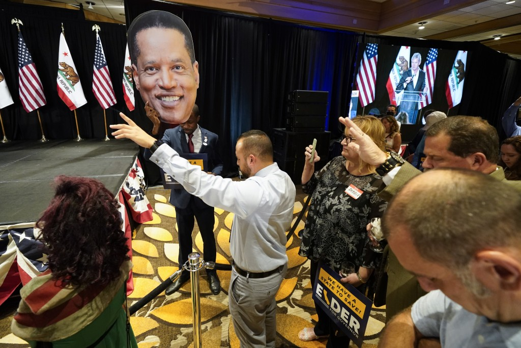 Supporters of Republican conservative radio show host Larry Elder pray while Errol Webber, center, holds up a cutout of Elder's face at a gathering as...