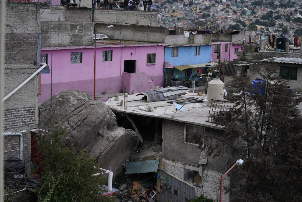 A boulder that plunged from a mountainside rests among homes in Tlalnepantla, on the outskirts of Mexico City, when a mountain gave way on Friday, Sep...